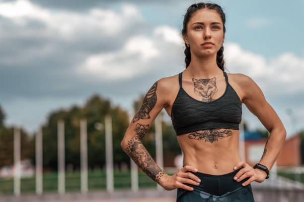frau sporttrainer, sommergadt, fitness-workout. motivationsstärke geist gedanken. tattoo-katzen auf figur. smart armband, uhr. freiraum. schönes mädchen am morgen auf der flucht. - gymnastik tattoo stock-fotos und bilder