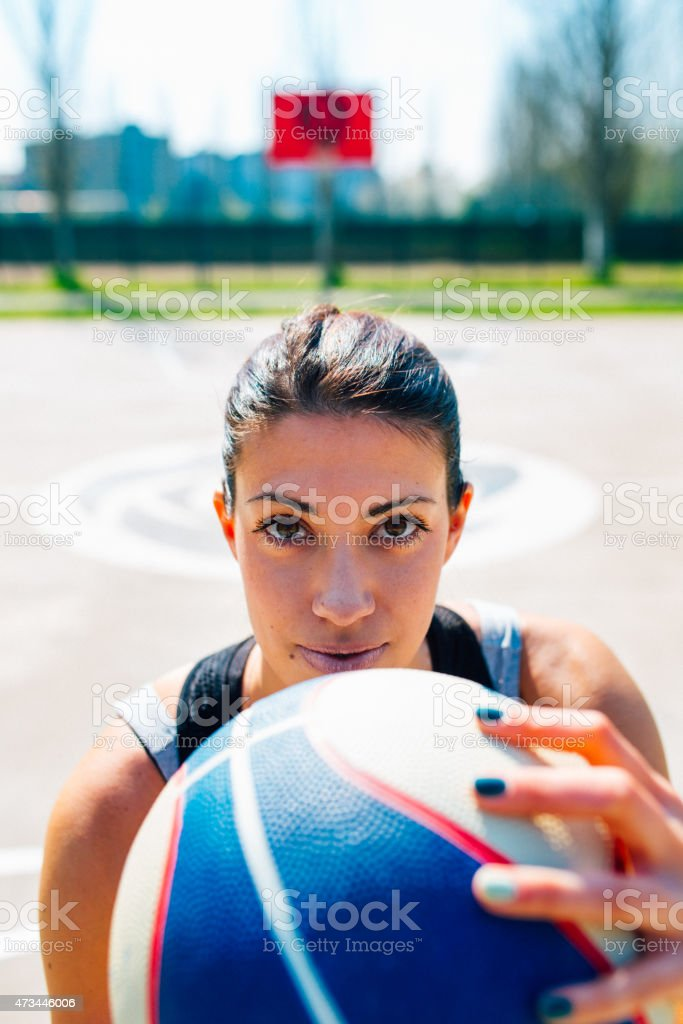 woman does sports training in the public basketball court. Shot for...