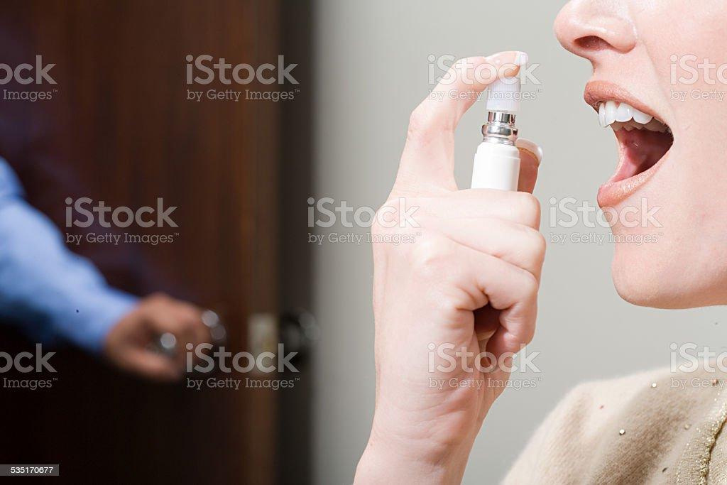 Woman spraying breath freshener stock photo