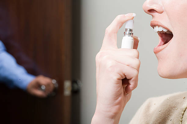 Woman spraying breath freshener stock photo