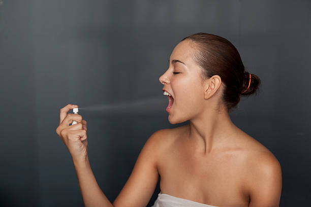 Woman spraying breath spray in her mouth stock photo