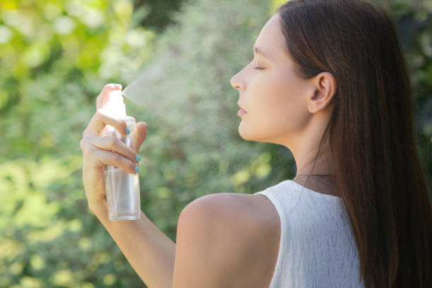 Woman spraying facial mist on her face, summertime skincare concept Woman spraying facial mist on her face, summertime skincare concept spraying stock pictures, royalty-free photos & images