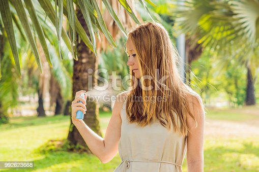 istock Woman spraying insect repellent on skin outdoor 992623668