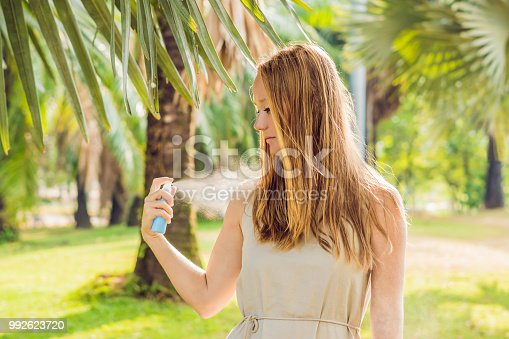 istock Woman spraying insect repellent on skin outdoor 992623720