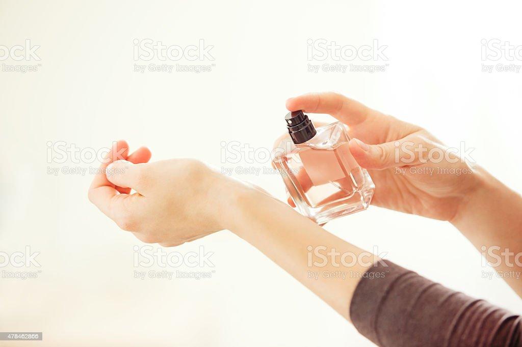 Woman spraying perfume on her wrist. stock photo