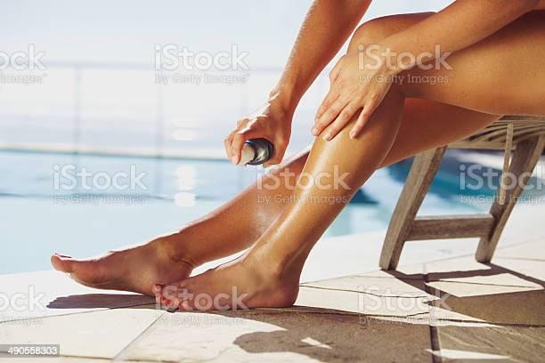 Mujer Pulverización Crema De Sol En Su Pierna Junto A La Piscina Foto de stock y más banco de imágenes de Rociado