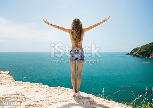 istock Woman spreading her Arms to the Sky on Vacation, Southern Thailand 973412328