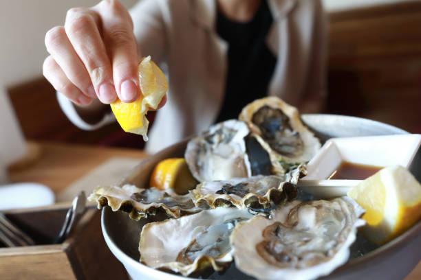 La mujer rocía ostras con jugo de limón en el restaurante - foto de stock