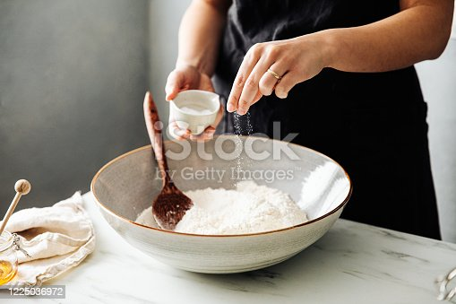 Midsection of woman sprinkling salt in flour before mixing. Female is preparing sourdough bread on marble counter. She is in kitchen.