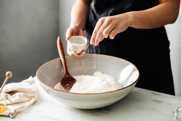 Woman sprinkling salt in flour before mixing Midsection of woman sprinkling salt in flour before mixing. Female is preparing sourdough bread on marble counter. She is in kitchen. salt stock pictures, royalty-free photos & images