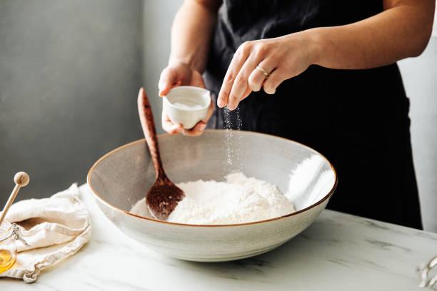 frau bestreuen salz in mehl vor dem mischen - alvarez stock-fotos und bilder