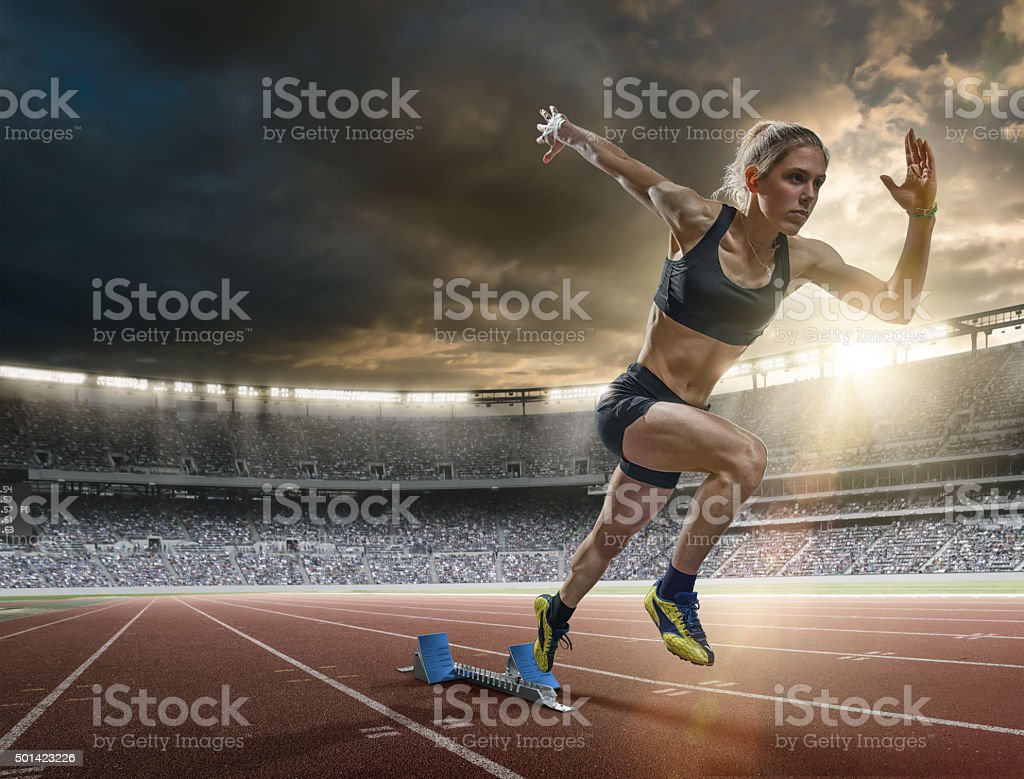 Woman Sprinter in Mid Action Bursting From Blocks During Race A mid action image of a woman sprinter during a sprint start from blocks on an outdoor athletics track. The athlete is running a generic outdoor floodlit athletics stadium full of spectators under a dark sky at sunset. The sprinter wears generic black sports top, shorts and running spikes.  100 Meter Stock Photo
