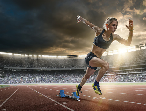 A mid action image of a woman sprinter during a sprint start from blocks on an outdoor athletics track. The athlete is running a generic outdoor floodlit athletics stadium full of spectators under a dark sky at sunset. The sprinter wears generic black sports top, shorts and running spikes.