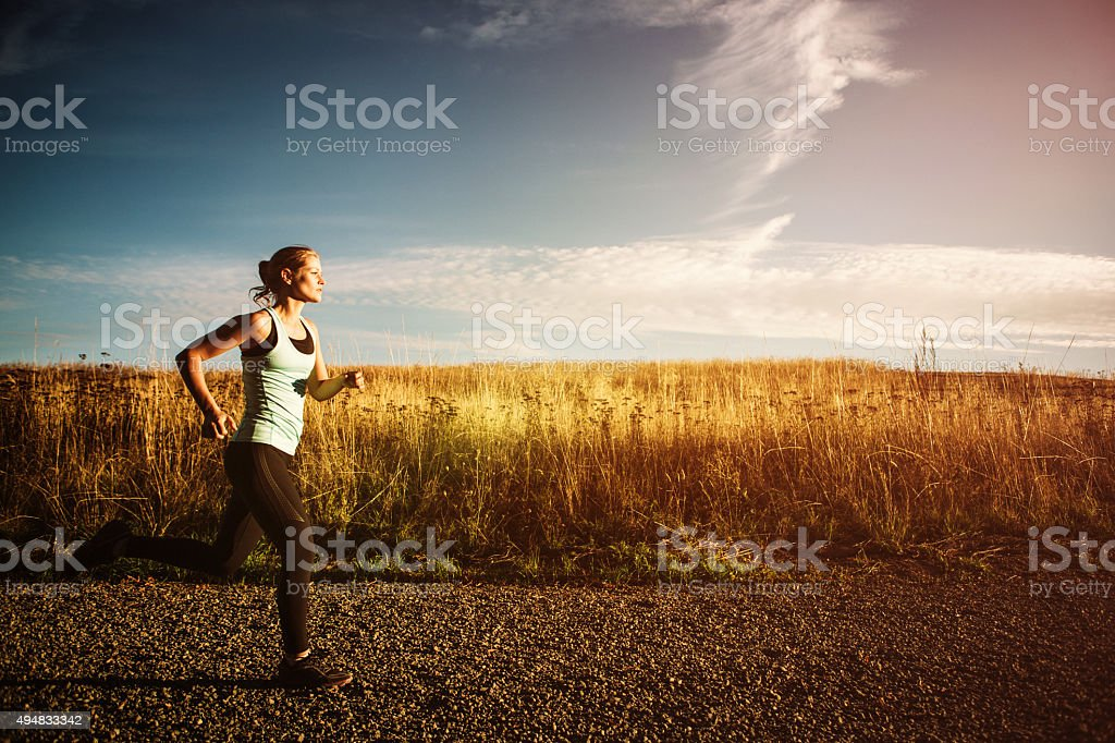 Woman Sprinting on Beautiful Sunset Road stock photo