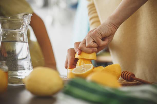 kobieta wyciskając cytrynę przy blacie kuchennym - cytryna zdjęcia i obrazy z banku zdjęć