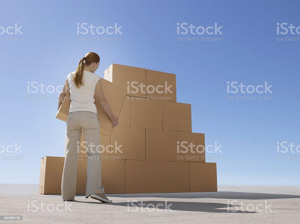 Woman stacking boxes in desert royaltyfri bildbanksbilder
