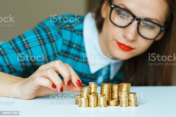 Woman stacking gold coins into columns picture id588357982?b=1&k=6&m=588357982&s=612x612&h=931kn qncu8ghv7uamqjsxgnc6yihf3guo7ztv2qlaa=
