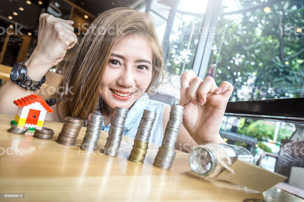 woman stacking gold coins into columns with house mode stock photo