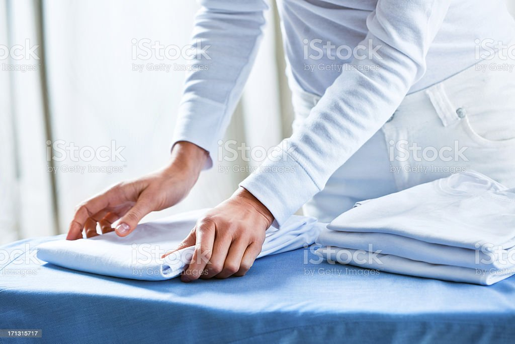 Woman Stacking Ironed Folded Shirts royalty-free stock photo