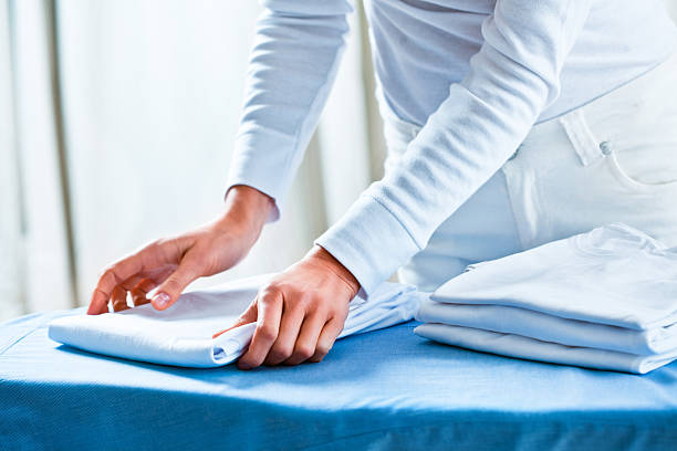 woman stacking ironed folded shirts - ironing stock photos and pictures
