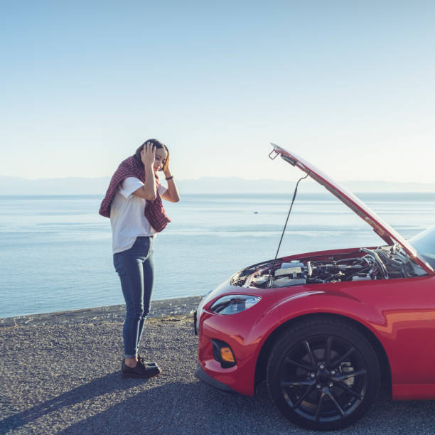 woman stand by the broken car woman stand by the broken car and don't know what to do at San juan island,USA. vehicle hood stock pictures, royalty-free photos & images