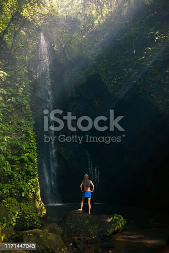 Young woman travel in Bali rainforest. Happy girl enjoy jungle nature. Stand in natural pool under waterfall, see on falling water. Walking day tour, hiking activity adventure on family summer holiday