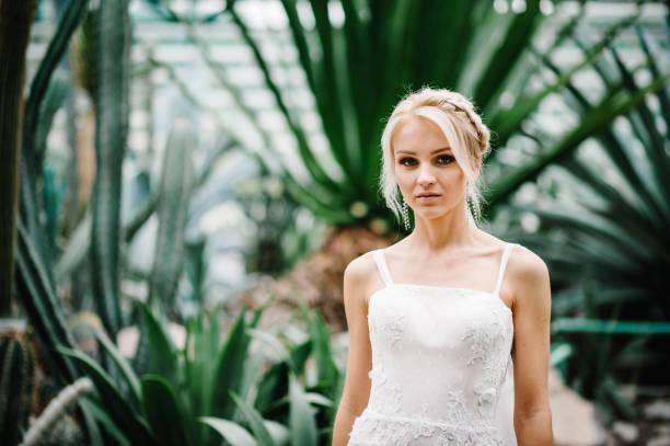 frau stand in den botanischen garten voller grün grün. hochzeits-zeremonie. porträt attraktive blonde braut stehen in einem brautkleid auf dem hintergrund von grün. - hochzeitsfrisur boho stock-fotos und bilder