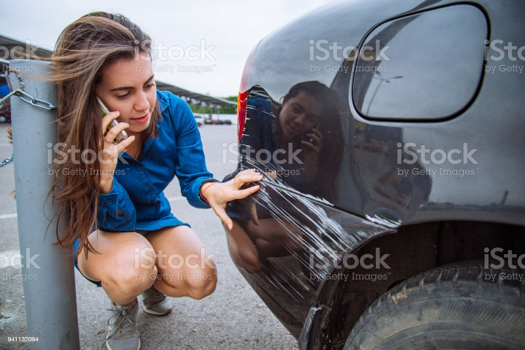 woman stand near scratched auto. call for help. car insurance stock photo