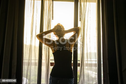istock Woman stand on the door while looking out of the window - back of silhouette woman 664693046