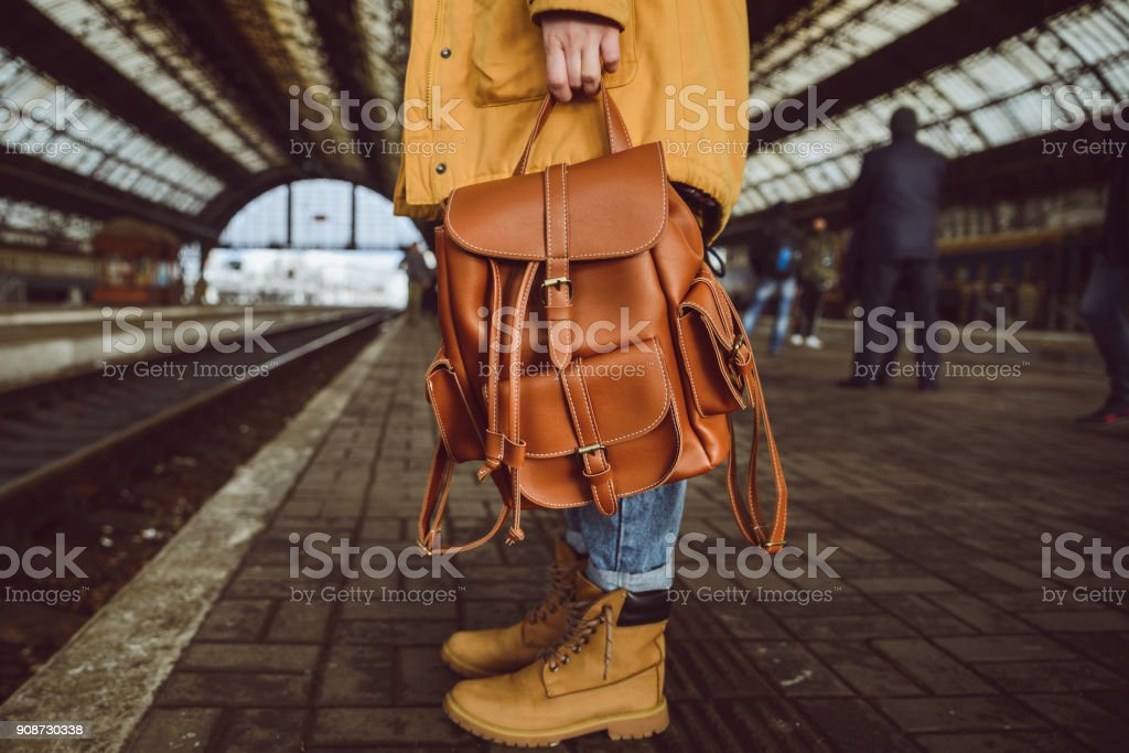 woman stand on the railway station hold backpack stock photo