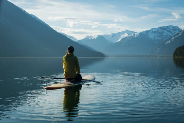 Frau Stand-up Paddle boarding auf einem unberührten Bergsee – Foto