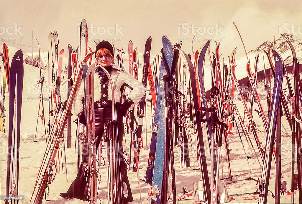 woman standind sorrounded by skis stock photo