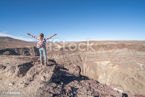Woman standing above canyon arms outstretched enjoying freedom in nature; girl hiking arms open on top of mountain