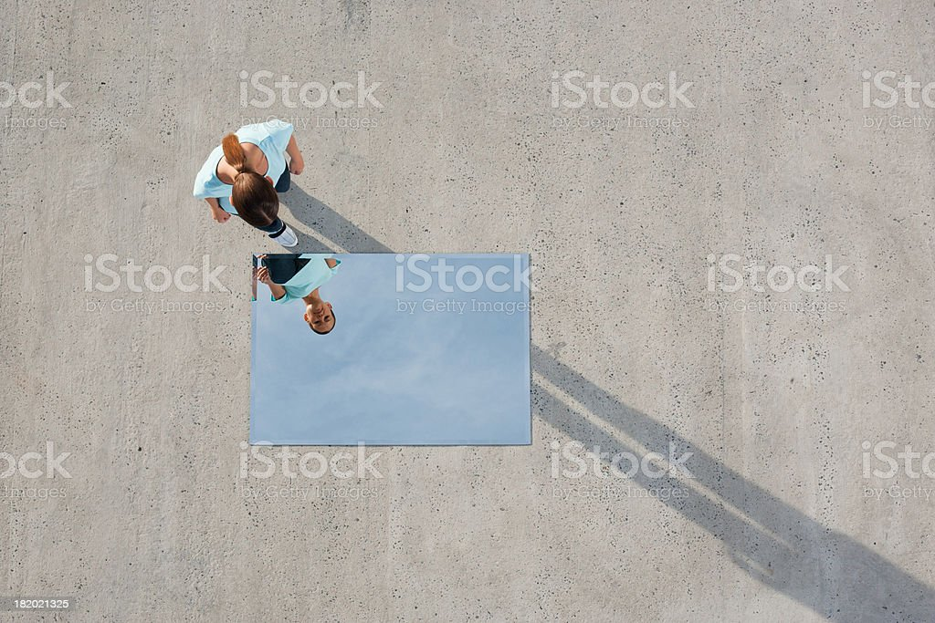 Woman standing above mirror and reflection outdoors