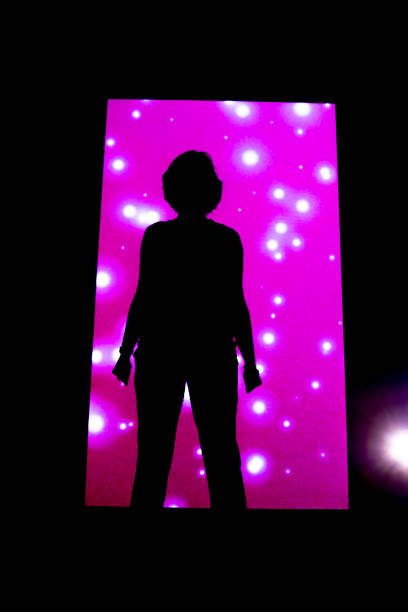 Woman Standing Against an Illuminated Pink Wal stock photo