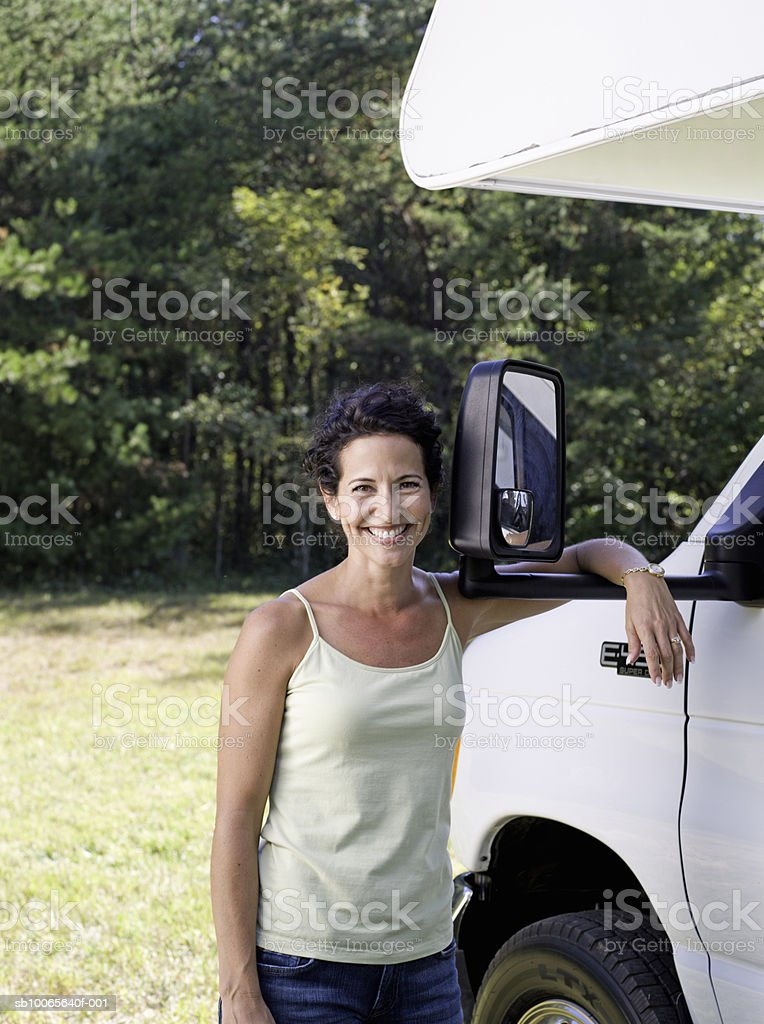 Woman standing against motorhome, smiling, portrait Lizenzfreies stock-foto