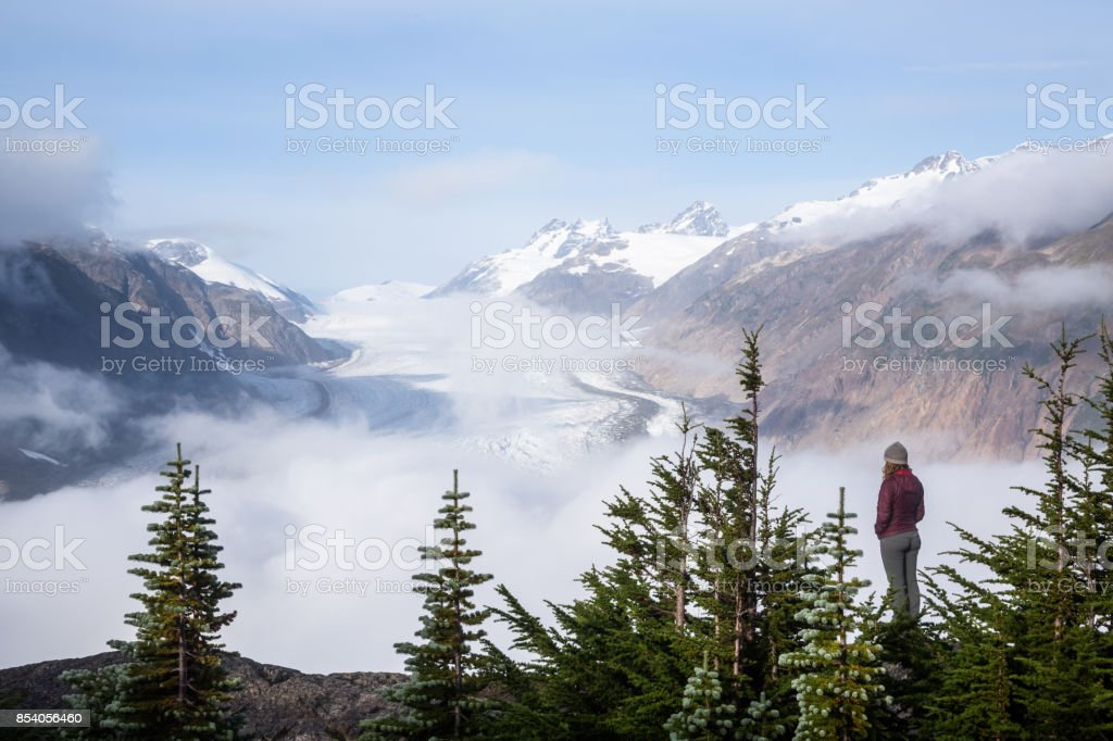 Woman standing among evergreen trees overlooking the foggy Salmon Glacier stock photo