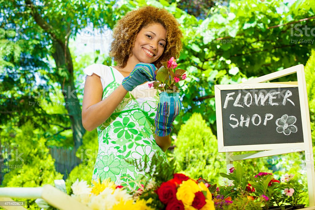 Woman Standing and cleaning plants outside florist. stock photo