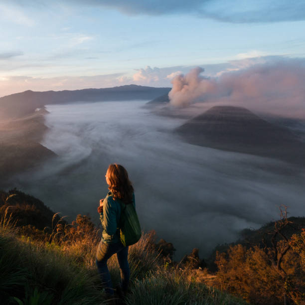 Woman standing and looking at  Bromo volcano at sunrise stock photo