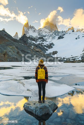 Young Caucasian woman standing and looking at Fitz Roy mountain in Patagonia