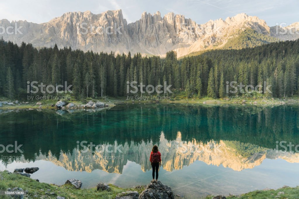 Woman standing and looking at  Lago di Carezza in Dolomites - Royalty-free Adulto Foto de stock