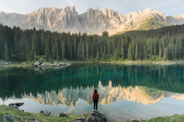 mujer de pie y mirando el lago di carezza en dolomitas - excursionismo fotografías e imágenes de stock