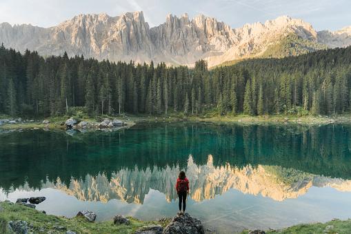 Woman Standing And Looking At Lago Di Carezza In Dolomites - Fotografie stock e altre immagini di Acqua