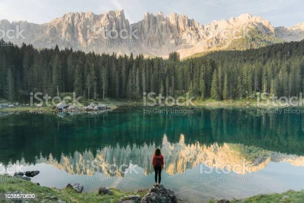 Woman Standing And Looking At Lago Di Carezza In Dolomites - Fotografias de stock e mais imagens de Adulto