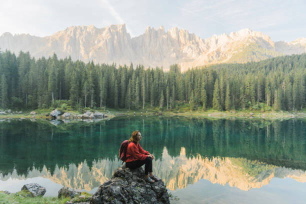 woman standing and looking at  lago di carezza in dolomites - latemar foto e immagini stock