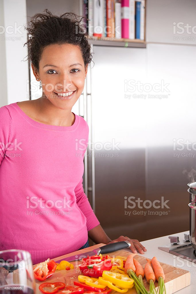 Woman standing and smiling in a kitchen royalty-free stock photo