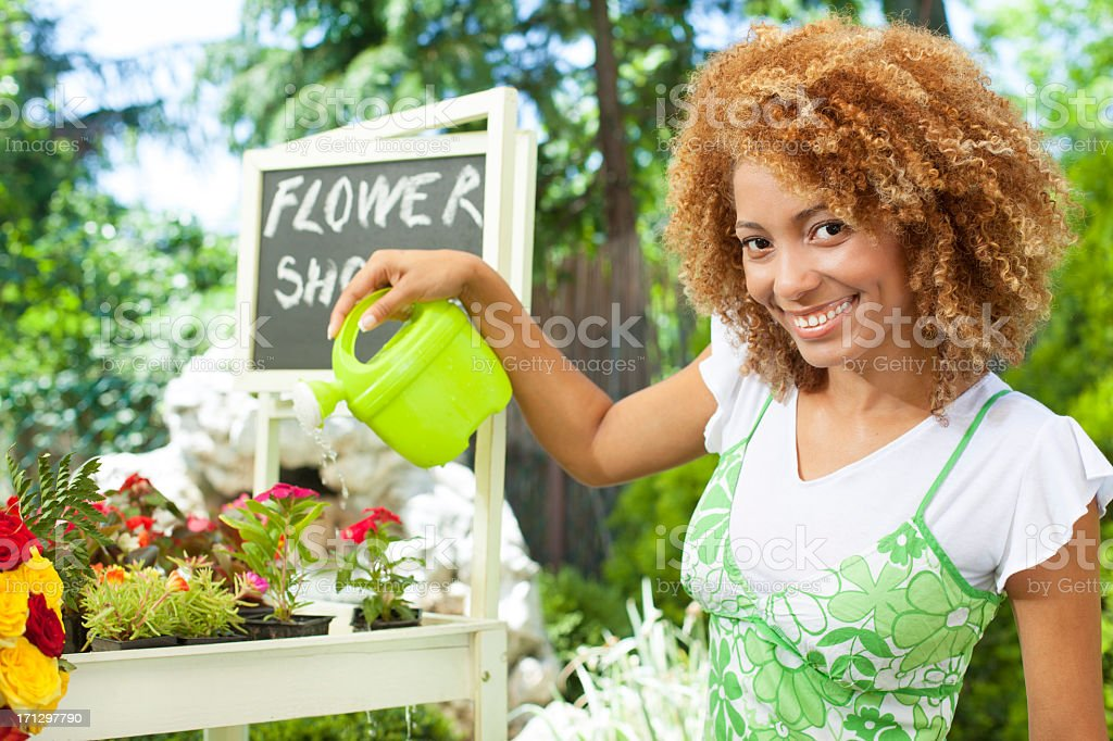 Woman Standing and watering plants outside florist. stock photo