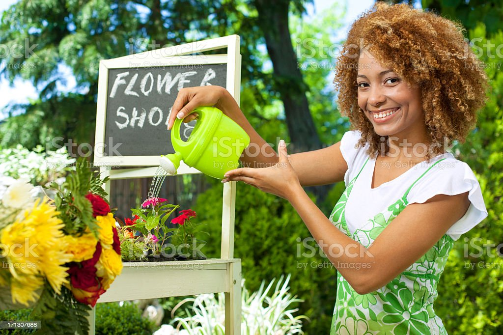 Woman Standing and watering plants outside florist. royalty-free stock photo