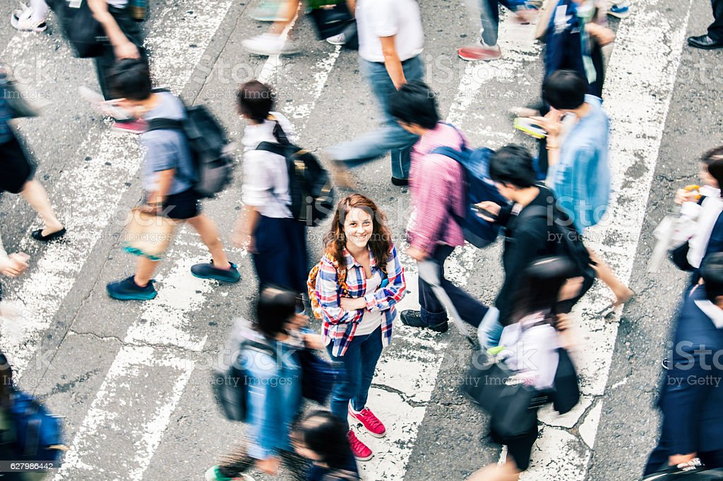 Woman standing arms crossed in the middle of pedestrians crossing...