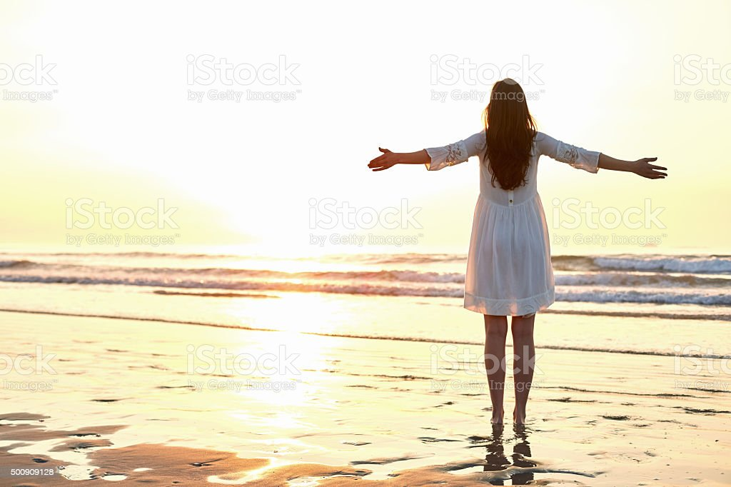 Woman Standing Arms Outstretched On Beach During Sunset